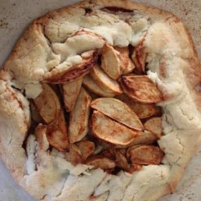 Rustic apple pie on a baking sheet.
