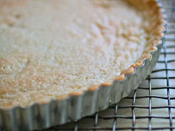 Gluten-free tart shell in pan on cooling rack.