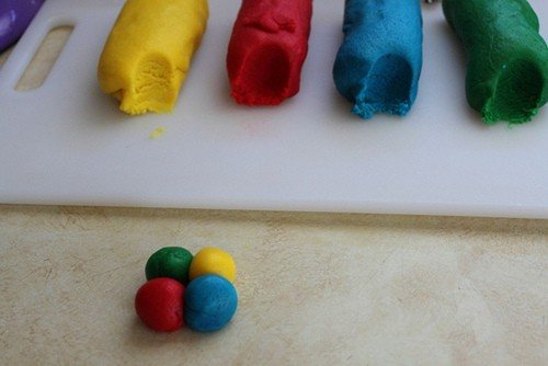 Yellow, red, blue, and green logs of gluten-free cookie dough. Four balls are together to make one cookie.