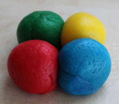 Green, yellow, blue, and red balls of gluten-free cookie dough.