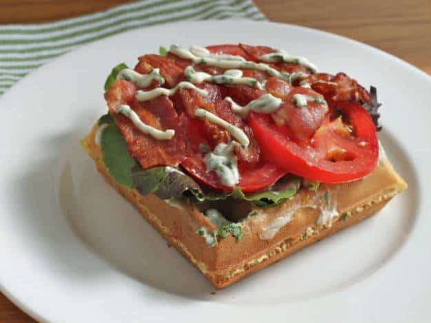 Gluten-Free Waffle BLT on a white plate. BLT is drizzled with basil mayo.
