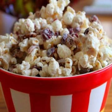 White chocolate popcorn with cranberries in a bowl.