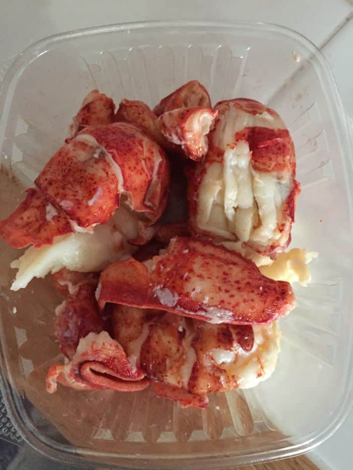 Lobster meat in small plastic container.