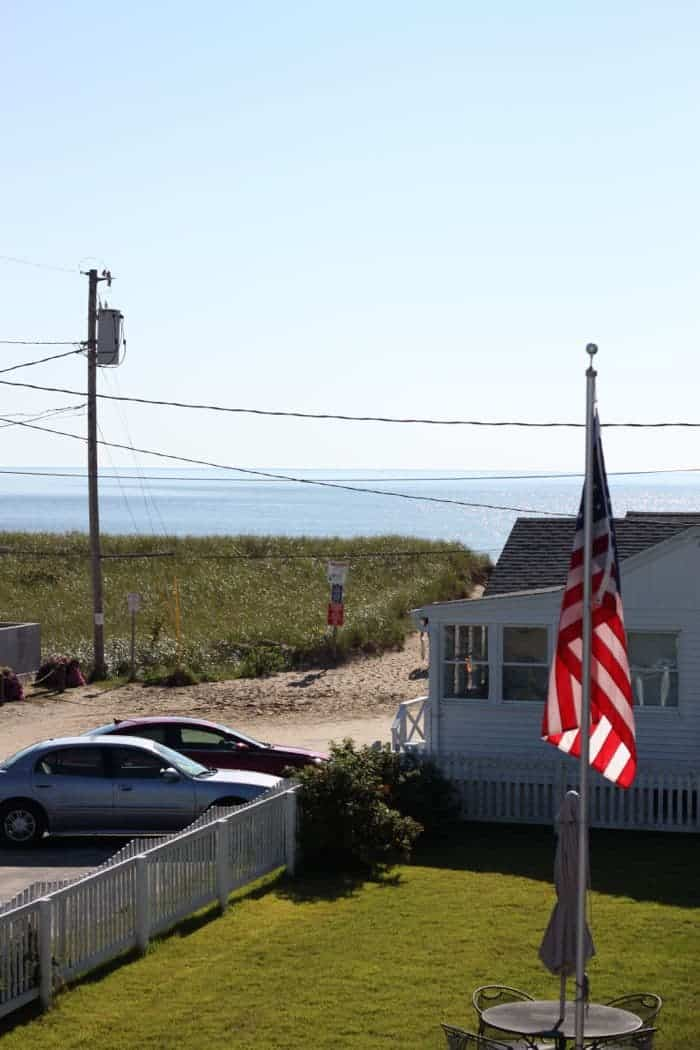 American flag on pole. Ocean in the distance.
