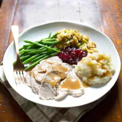 Gluten-free gravy on turkey on a plate of Thanksgiving food.