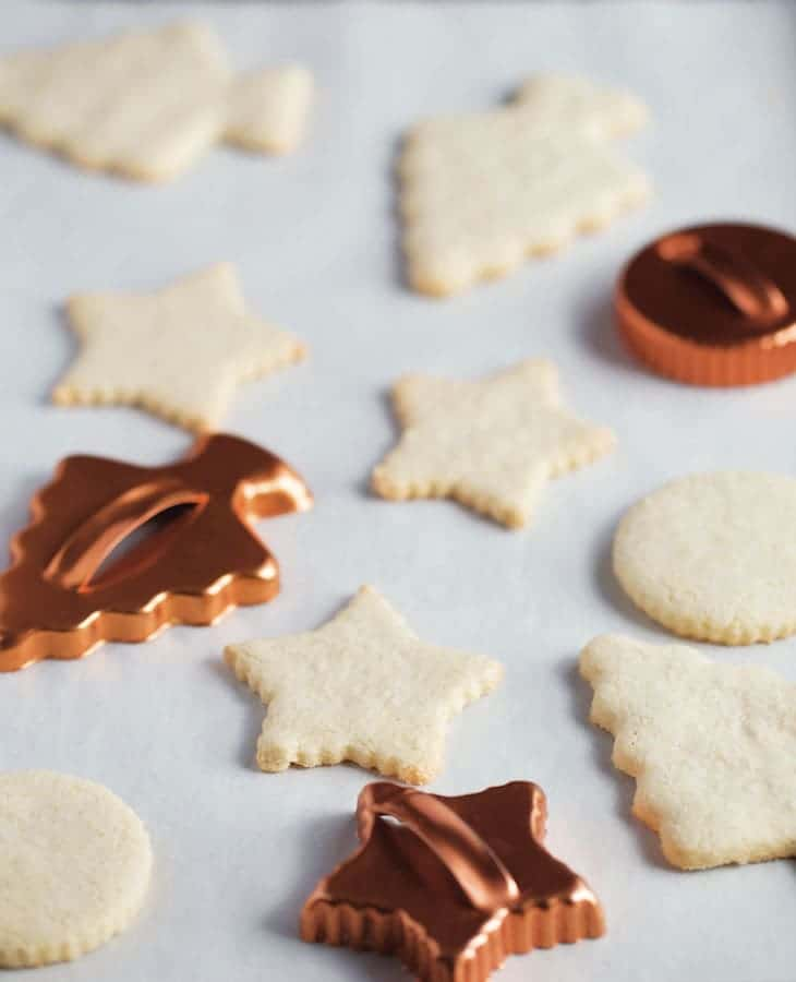 Baked paleo sugar cookies on a pan with three cookie cutters.