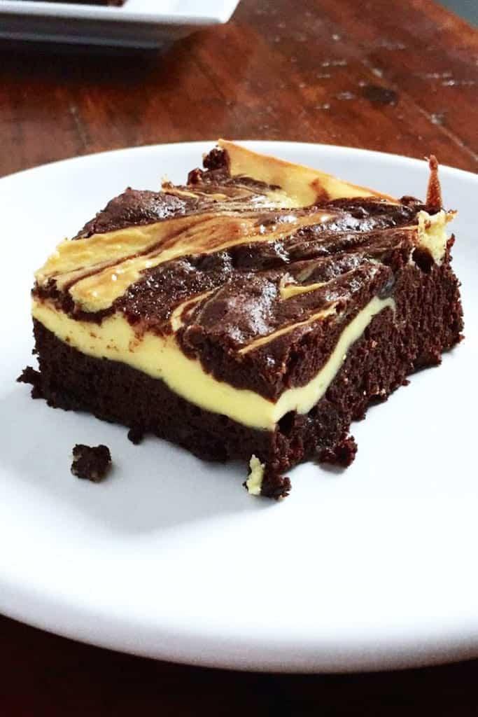 Gluten-free cheesecake brownie on white plate.