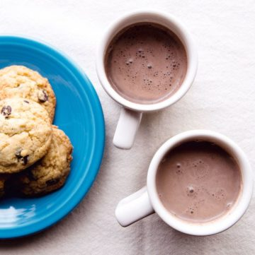 Dairy-free hot chocolate in two mugs. Small plate of chocolate chips on the left.