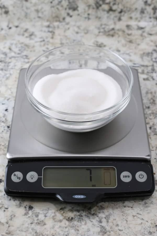 Granulated sugar in glass bowl on digital scale. Display reads 7 ounces.