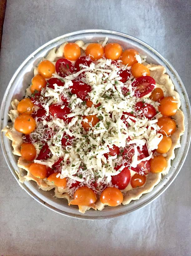 Unbaked gluten-Free tomato pie topped with shredded cheese.