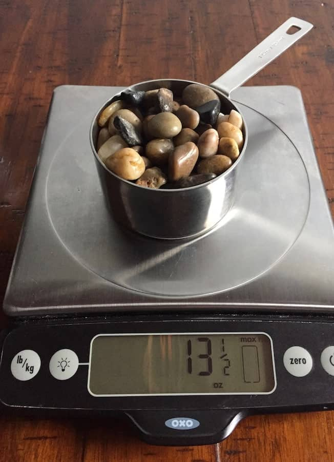 Cup on stones on a digital scale. Display reads 13 1/2 ounces.