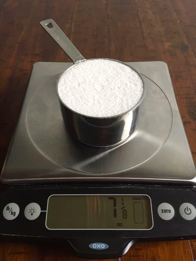 Granulated sugar on a digital scale. Display reads 7 1/8 ounces.