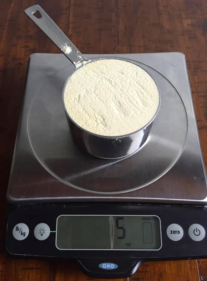 Cup of brown rice flour on a digital scale. Display reads 5 ounces.