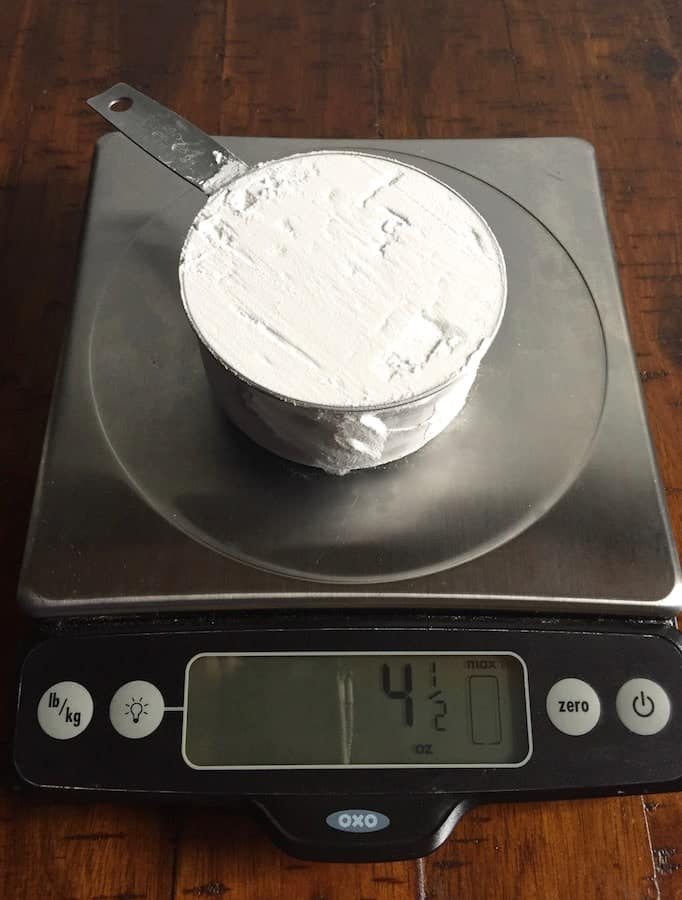 Cup of tapioca starch on a digital scale. Display reads 4 1/2 ounces.