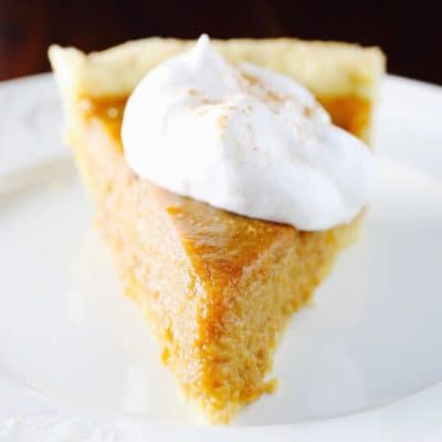 Gluten-Free Sweet Potato Pie topped with whipped cream on a white plate.