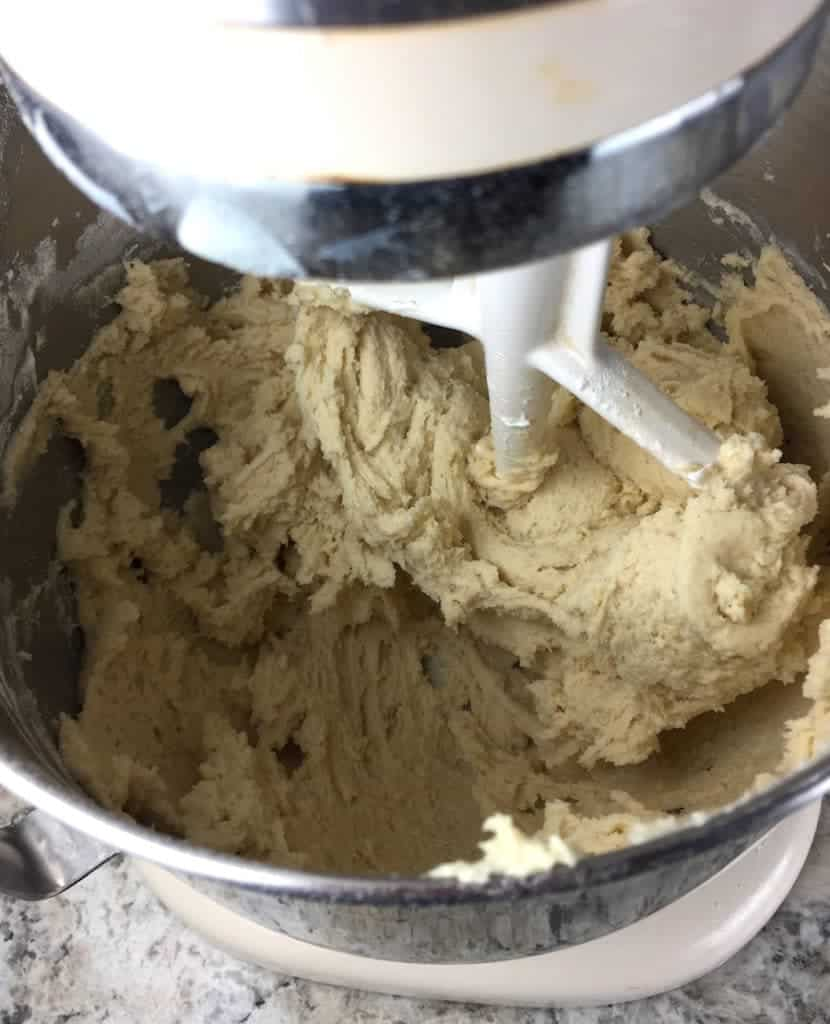 Gluten-free soft sugar cookie dough in bowl of a stand mixer.