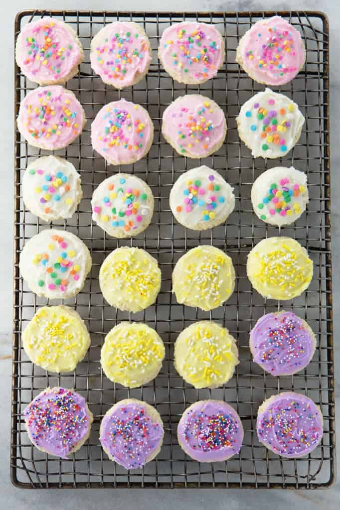 Gluten-Free Soft Sugar Cookies on a wire rack. Cookies are frosted with buttercream and and topped with sprinkles.
