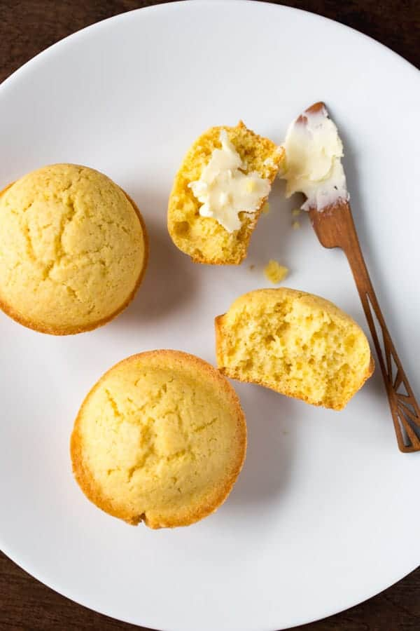 Gluten-free corn muffins on a white plate. One is split and spread with butter.
