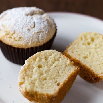 Gluten-free sour cream muffins topped with powdered sugar. One is split to show texture.