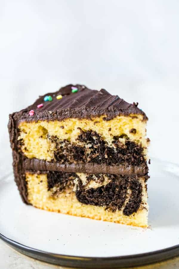 Slice of gluten-free marble cake, frosted with chocolate frosting, on a white plate.