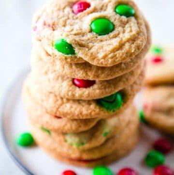 Gluten-free M&Ms cookies with red and green M&Ms on a plate.
