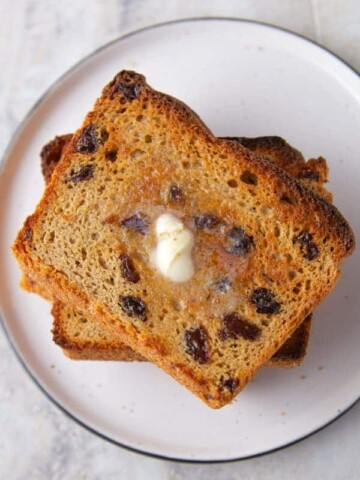 Stack of toasted cinnamon raisin bread slices. Melted butter on top slice.