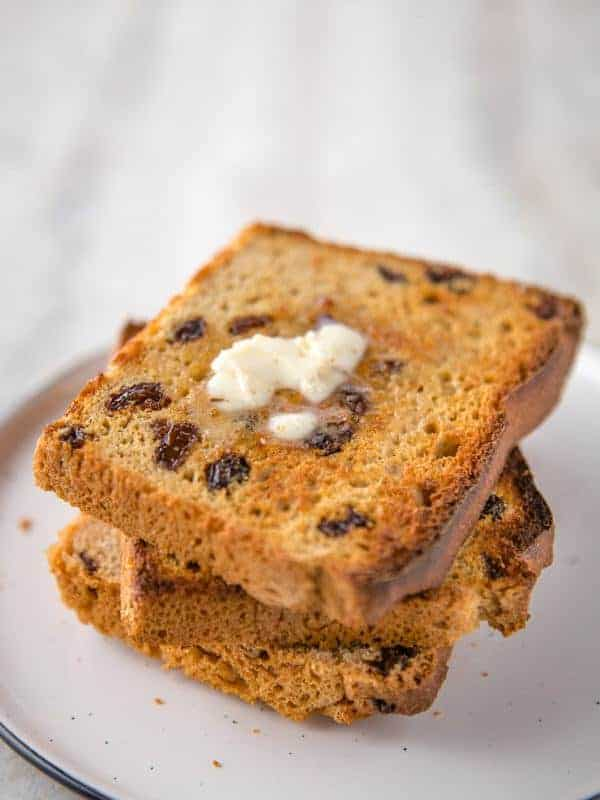 Stack of Toasted Gluten-Free Cinnamon Raisin Bread. Top slice is buttered.
