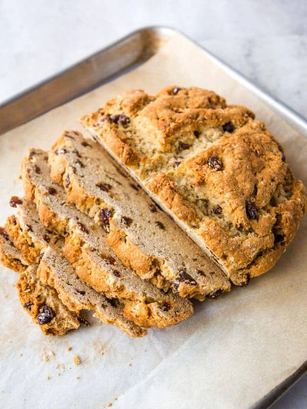 Loaf of Irish Soda Bread sliced on a sheet pan. The bread contains raisins and caraway seeds.