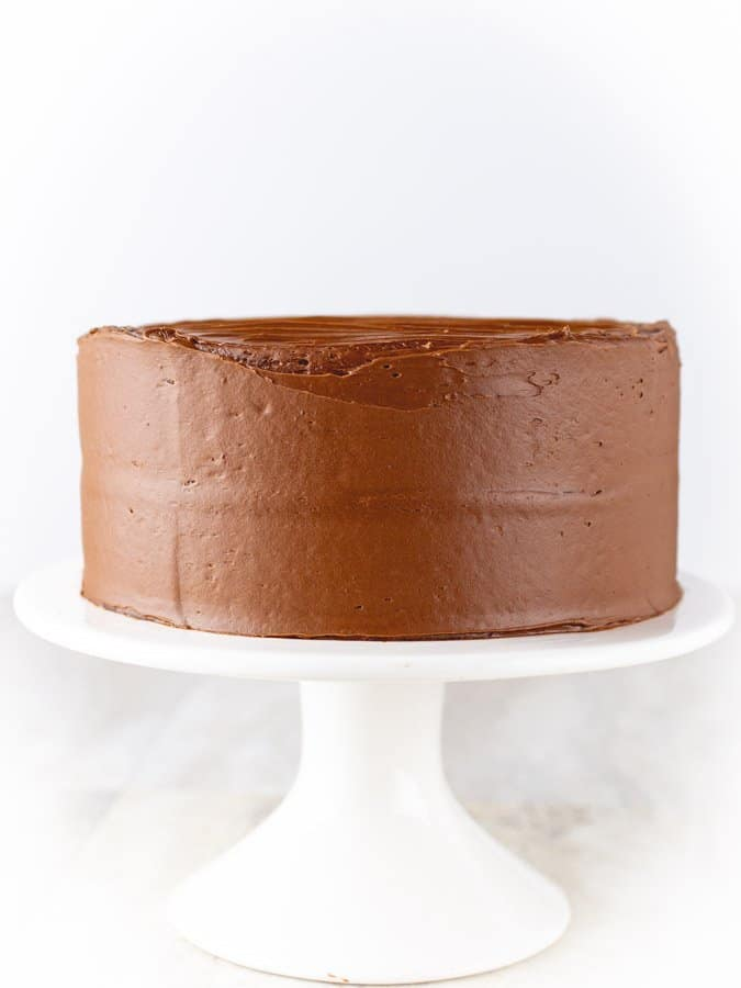 Gluten-Free Chocolate Cake on a white cake stand.