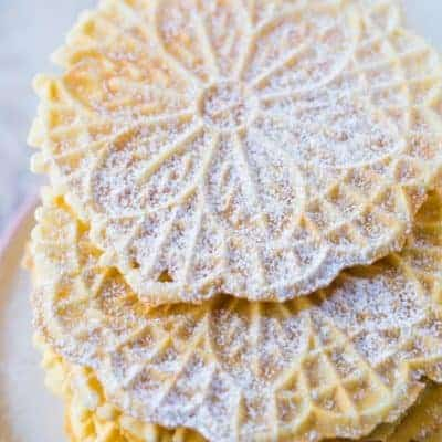 Stack of Baked Pizzelles Dusted with Powdered Sugar
