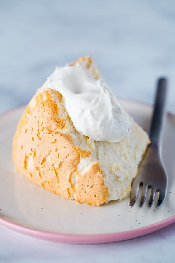Slice of Gluten-Free Angel Food Cake on Plate with a Dollop of Whipped Cream