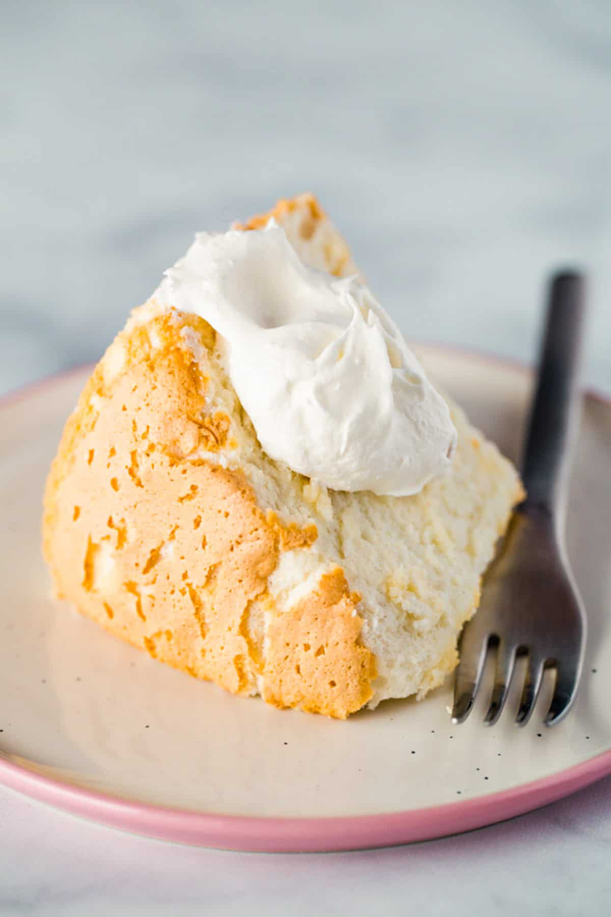 Gluten-free angel food cake with whipped cream on plate.