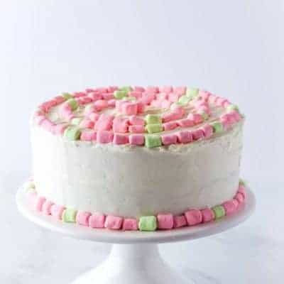 Gluten-Free Strawberry Cake on a white platter. Frosted with cream cheese frosting and decorated with pink and green mini-marshmallows.
