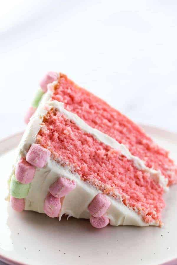 Gluten-Free Strawberry Cake Slice on Plate. Frosted with cream cheese frosting and decorated with pink and green marshmallows.