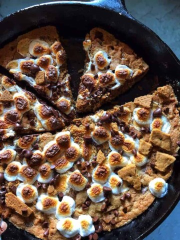 Gluten-Free S'more Cookie in Skillet. Cut and topped with browned marshmallows and chocolate chips.
