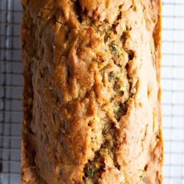 Loaf of baked gluten-free zucchini bread on a cooling on a rack.