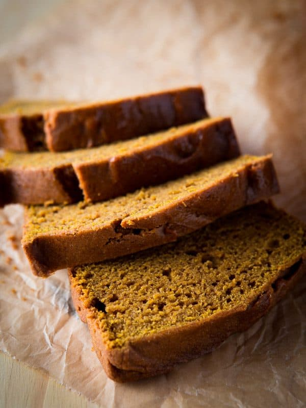 Sliced gluten-free pumpkin bread on brown parchment paper