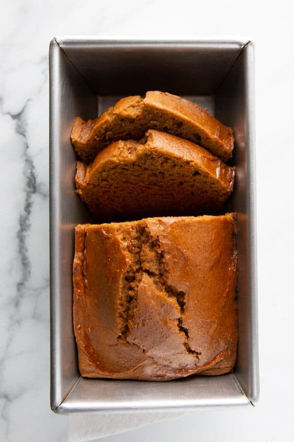 Baked gluten-free pumpkin bread in pan, sliced.