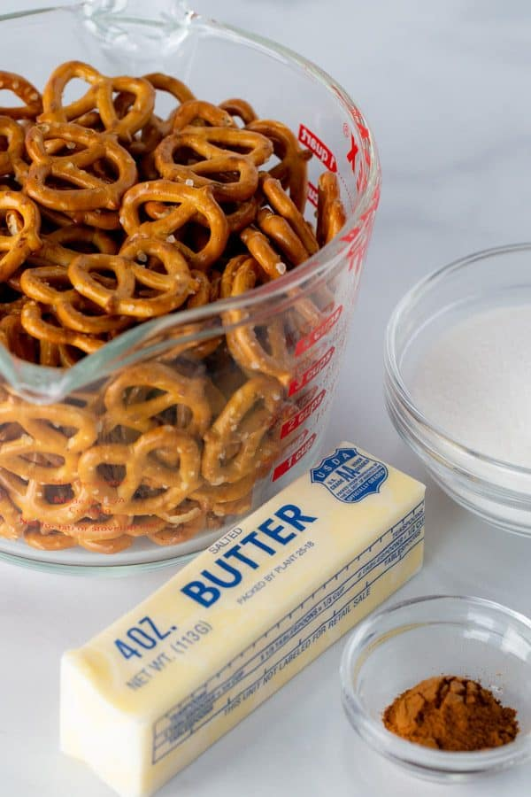 Measuring cup of pretzels. Stick of butter. Bowl of sugar. Small bowl of ground cinnamon.