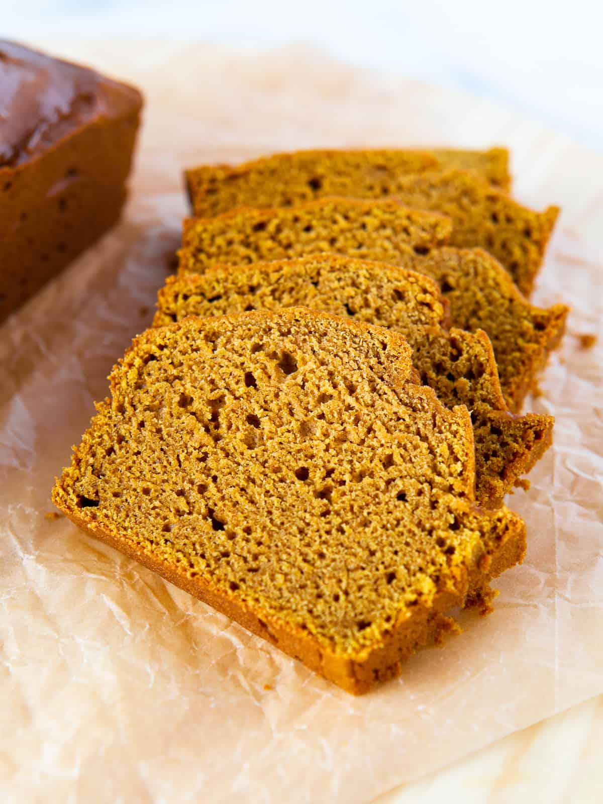 Sliced gluten-free pumpkin bread on a cutting board.