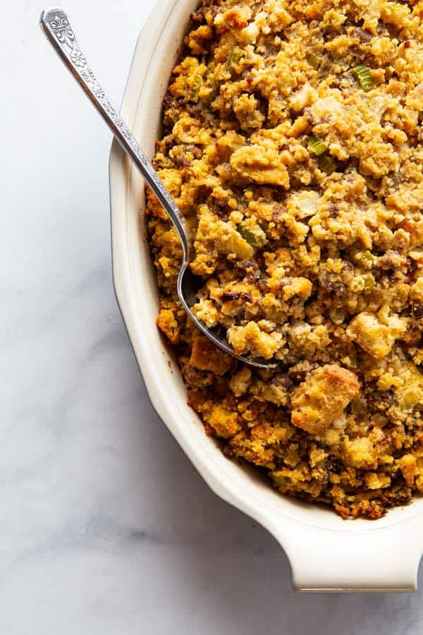 Baked gluten-free cornbread stuffing in a casserole dish with serving spoon.
