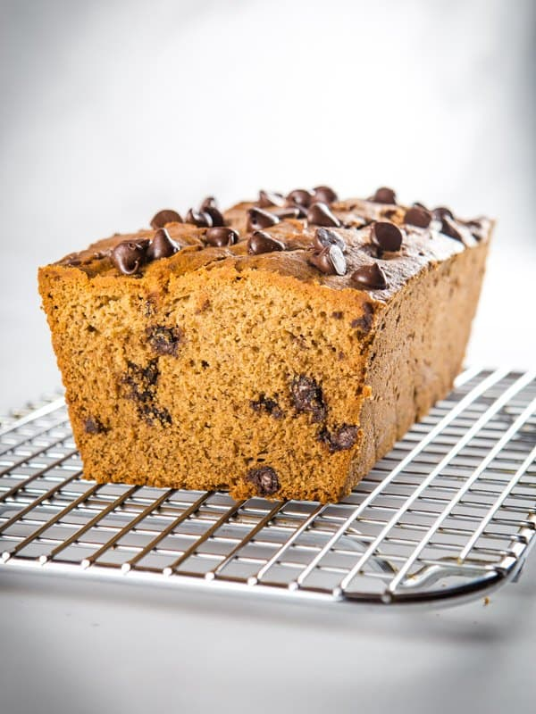 Baked gluten-free banana bread with chocolate chips on a cooling rack.