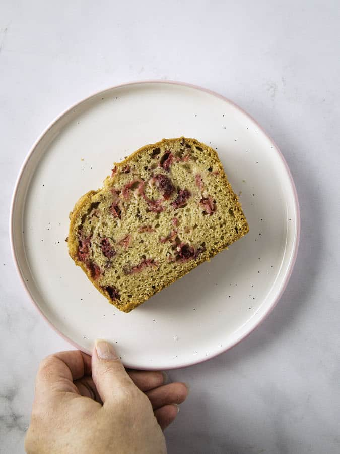 Slice of gluten-free cranberry bread on a plate.