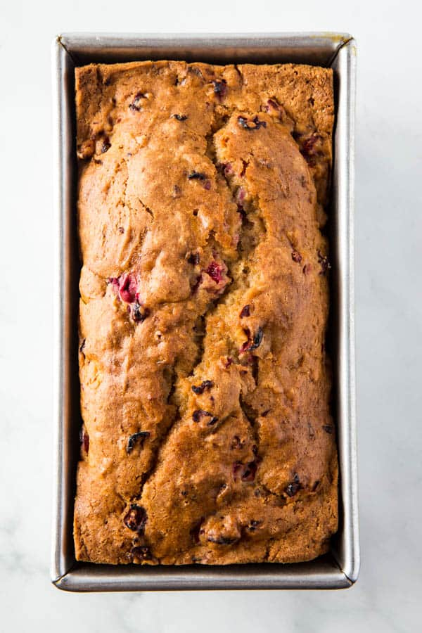 Baked loaf of gluten-free cranberry bread in pan.