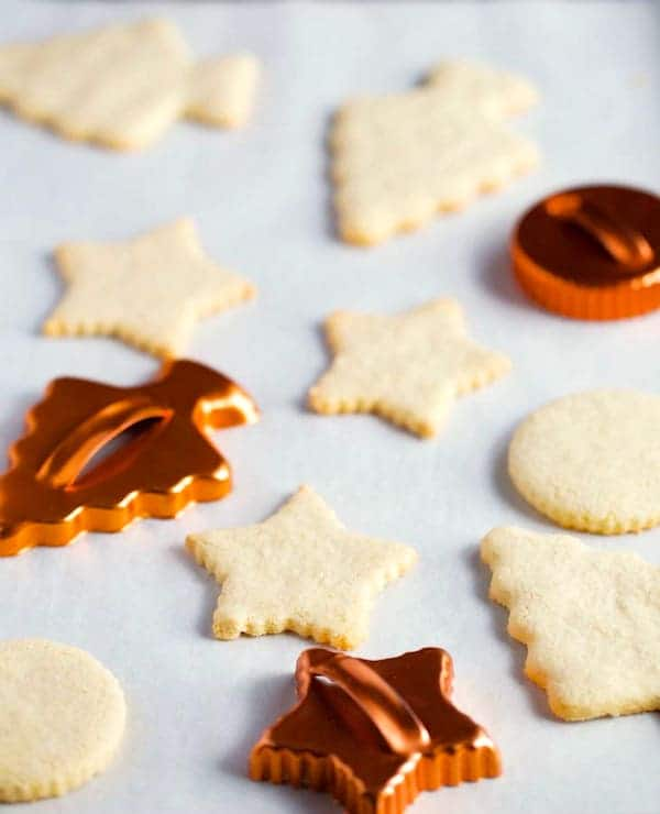 Baked paleo sugar cookies on a pan with two cookie cutters.