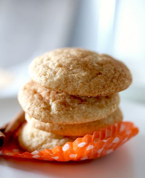 Stack of baked gluten-free snickerdoodles in a orange paper wrapper