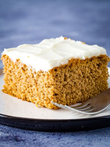 Slice of gluten-free spice cake with cream cheese frosting on plate.
