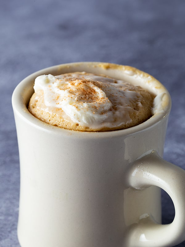 Mug with gluten-free spice mug cake in it. Frosted with cream cheese frosting and sprinkled with ground cinnamon.