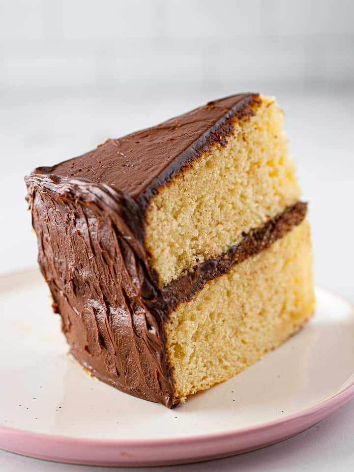Slice of gluten-free yellow cake with chocolate frosting