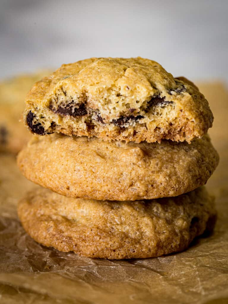 Stack of gluten-free chocolate chip cookies. Top cookie is broken in half to show texture.